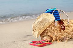 Summer beach bag on sandy beach. Summer beach bag with straw hat,towel,sunglasses and flip flops on sandy beach Stock Photo
