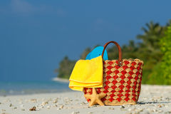 Summer beach bag with shell, towel on sandy beach Stock Photo