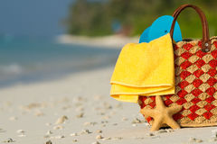 Summer beach bag with shell, towel on sandy beach Royalty Free Stock Images