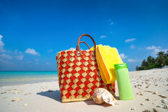 Summer beach bag with shell, towel on sandy beach Royalty Free Stock Photography