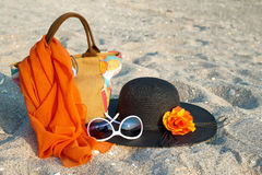 Summer beach bag with straw hat. Sunglasses and scarf on sandy beach Royalty Free Stock Image