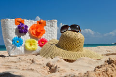 Summer beach bag with straw hat and sunglasses. On sandy beach Royalty Free Stock Images