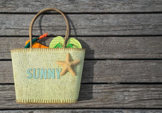 Summer beach bag with text sunny on wood background. Concept of leisure and travel Stock Images
