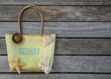 Summer beach bag with text sunny on wood background. Royalty Free Stock Image