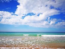 Summer beach with blue sea and waves, amazing blue sky with white clouds. Spain stock photography