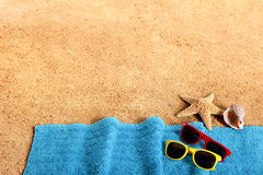 Summer beach border, sand background, sunglasses, copy space. Beach background border with sunglasses, towel, starfish and seashells. Copy space Royalty Free Stock Image