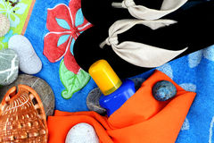 Summer beach composition, punchy colours. Top view of a composition with a pair of beach sandals, some seashells, some stones and a sunscreen, on a beach towel Royalty Free Stock Image