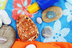 Summer beach composition, vintage style. Top view of a composition with a big seashell, some stones and a sunscreen, on a beach towel, vintage style, small depth Stock Image
