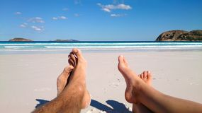 Summer and beach concept - couple lying on beach. Summer and beach concept - Feet of couple lying on the white beach in western australia stock image