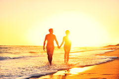 Summer beach couple romantic holding hands sunset. Summer beach couple romantic holding hands at sunset walking in love on honeymoon travel vacation holidays Stock Photography