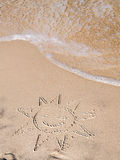 Summer on the beach. Finger drawn sun on sandy beach royalty free stock photos