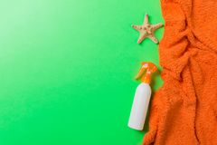 Summer beach flat lay accessories. Sunscreen bottle cream, towel and seashells on colored Background. Travel holiday concept with. Copy space royalty free stock photos