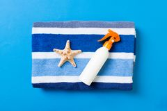 Summer beach flat lay accessories. Sunscreen bottle cream, towel and seashells on colored Background. Travel holiday concept with. Copy space stock image