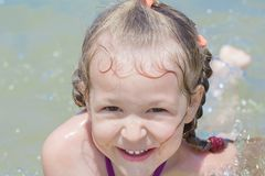 Summer beach fun of little girl kid splashing and floating in sea stock images