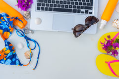 Summer beach fun. Mock up -laptop with swimming suit, sandals, sunglasses and sunscreens Stock Image