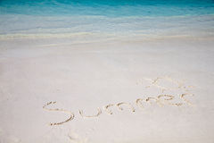 Summer on the beach. Handwriting of summer word on white sand beach backgrounded with clear blue sea Stock Photography