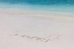 Summer on the beach. Handwriting of summer word on the beach backgrounded with clear blue sea Royalty Free Stock Image