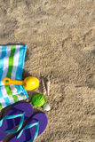 Summer beach holiday. Beach background with flip flop, towel and plastic spade Royalty Free Stock Photography