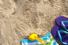 Summer beach holiday. Beach background with flip flop, towel and plastic spade Royalty Free Stock Images