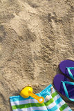 Summer beach holiday. Beach background with flip flop, towel and plastic spade Stock Photography