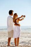 Summer beach honeymoon. Couple standind on the sand and taking pictures of the beautiful sunset over the ocean Stock Image