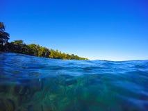 Summer beach landscape through sea water, clean blue sea water look through, Stock Photography