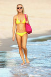 Summer/beach lifestyle. Lady in yellow bikini with pink shoulder bag strolling along the water's edge of the ocean late afternoon Royalty Free Stock Photo