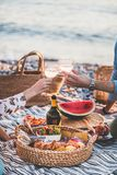 Couple having picnic at seaside and clinking glasses with wine. Summer beach picnic at sunset. Young couple having weekend picnic outdoors at seaside with fresh stock image