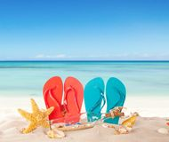 Summer beach with red sandals and shells Stock Photography