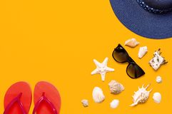 Summer beach sea accessories. Coral flip flops, blue straw hat, sunglasses, shells, starfish on yellow background top view flat. Lay copy space. Summer stock image