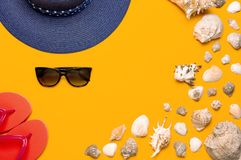 Summer beach sea accessories. Coral flip flops, blue straw hat, sunglasses, shells, starfish on yellow background top view flat. Lay copy space. Summer royalty free stock photos
