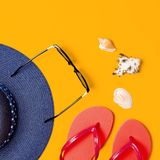 Summer beach sea accessories. Coral flip flops, blue straw hat, sunglasses, shells, starfish on yellow background top view flat. Lay copy space. Summer stock images