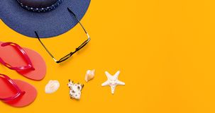 Summer beach sea accessories. Coral flip flops, blue straw hat, sunglasses, shells, starfish on yellow background top view flat. Lay copy space. Summer stock photos
