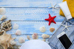 Summer beach sea concept. Blue Wooden background with different accessories, shells, starfish, towel, sunscreen, sand Royalty Free Stock Photo