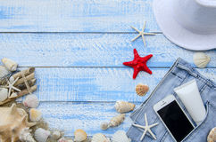 Summer beach sea concept. Blue Wooden background with different accessories, shells, starfish, towel, sunscreen, sand Royalty Free Stock Images