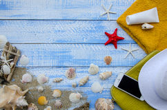 Summer beach sea concept. Blue Wooden background with different accessories, shells, starfish, towel, sunscreen, sand Royalty Free Stock Image