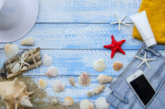 Summer beach sea concept. Blue Wooden background with different accessories, shells, starfish, towel, sunscreen, sand Stock Photo