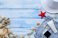 Summer beach sea concept. Blue Wooden background with different accessories, shells, starfish, towel, sunscreen, sand Stock Photos