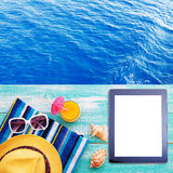 Summer beach, set of summer accessories and tablet. Workplace for freelancer Royalty Free Stock Photo