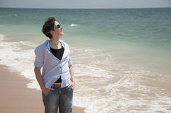 Summer on the beach. Smiling young person standing with hands in the pockets on a beach Stock Photography