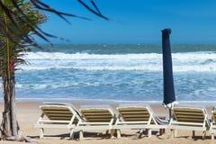 Summer beach sun chairs lounger near tropical sea Stock Image