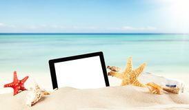 Summer beach with tablet in sand royalty free stock images