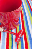 Summer beach towel red children's toys. Summer vacations at the seaside concept. Stripy beach towel and children's toys: red bucket and rake royalty free stock image