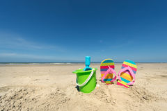 Summer beach. With toys and flip flops Royalty Free Stock Photos