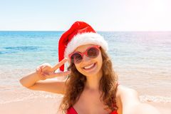 Summer beach vacation girl in santa hat taking fun mobile selfie photo with smartphone. Girl wearing red sunglasses posing for sel stock photography