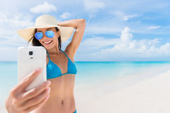 Summer beach vacation girl taking fun phone selfie. Summer beach vacation girl taking fun mobile selfie photo with smartphone. Cute Asian woman wearing blue stock images