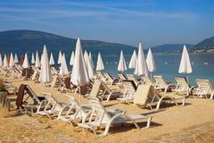 Summer beach vacation. Sunny Mediterranean landscape with white beach umbrellas. Montenegro, Adriatic Sea, Bay of Kotor. Near Tivat city royalty free stock photos