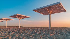 Summer beach with white wooden umbrellas in the sunset sunshine. Holidays by the sea. Summer beach with white wooden umbrellas in the sunset sunshine. Beautiful royalty free stock images