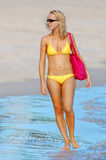 Summer beach woman. Lady in yellow bikini with pink shoulder bag strolling along the beach at the waters edge. The beautiful tropical island lifestyle is evident royalty free stock photography