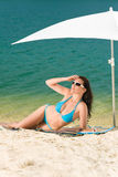 Summer beach woman blue bikini under parasol Royalty Free Stock Photo